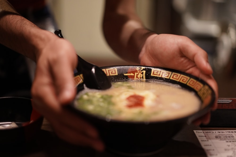 shallow focus photo of soup in black ceramic bowl
