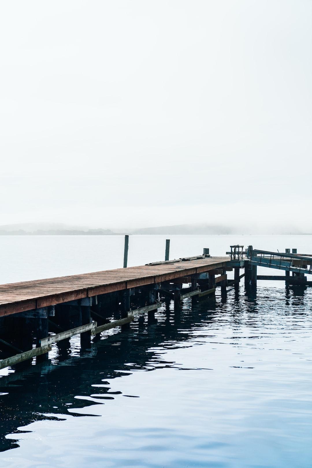 Reflections of a long wooden dock along a foggy coastline.