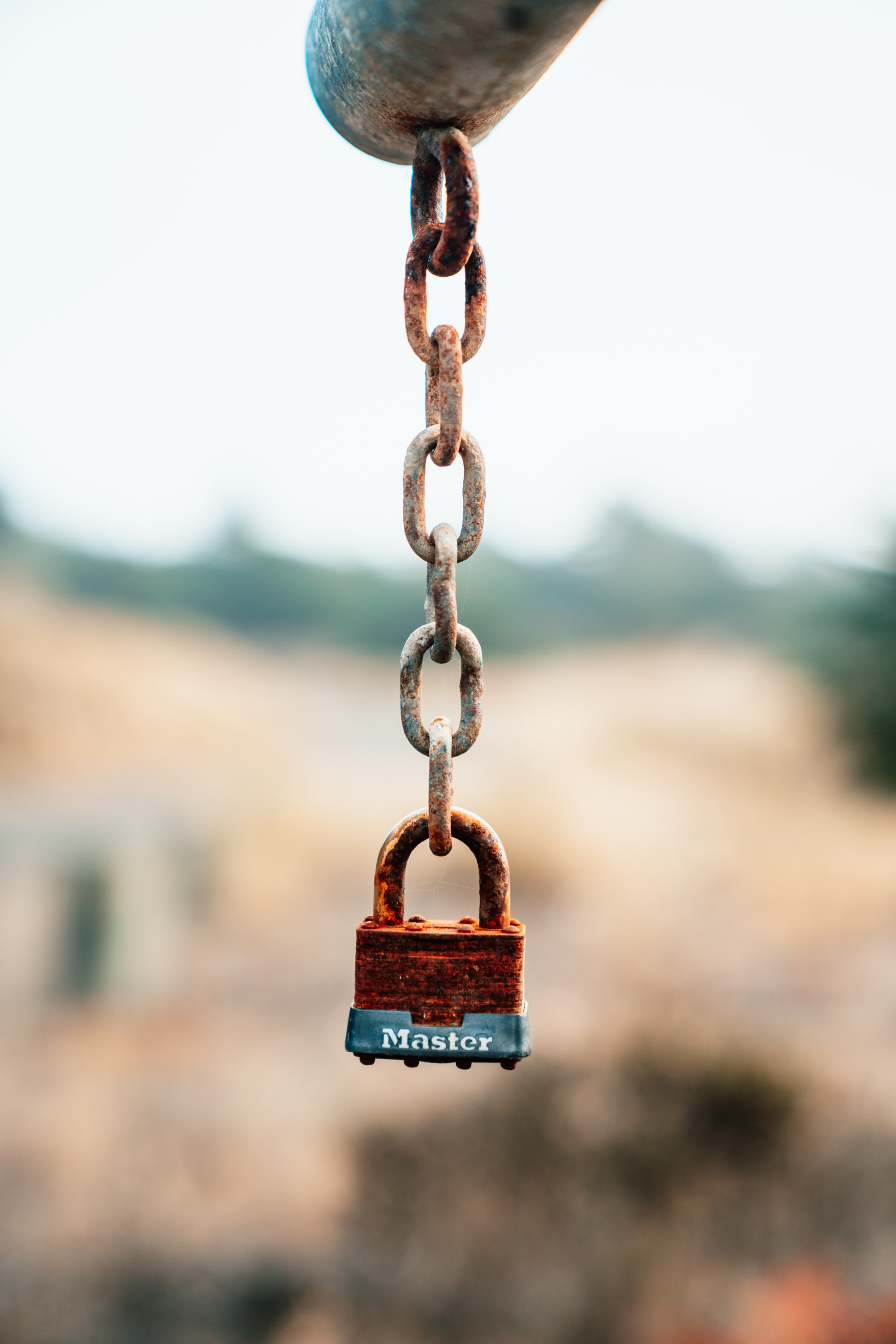 Rusted Master padlock hanging on the old chain of a state park gate.