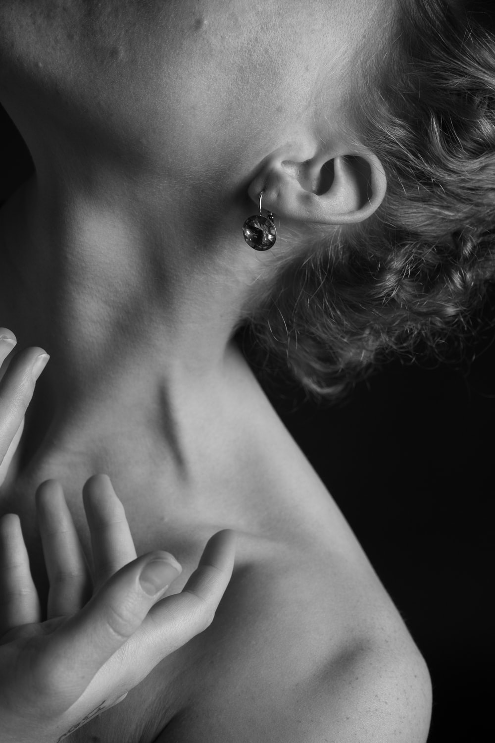 grayscale photography of topless person wearing earring