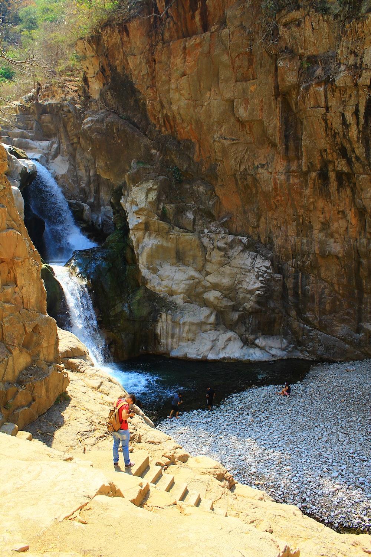 person standing on rocky mountain near waterfalls