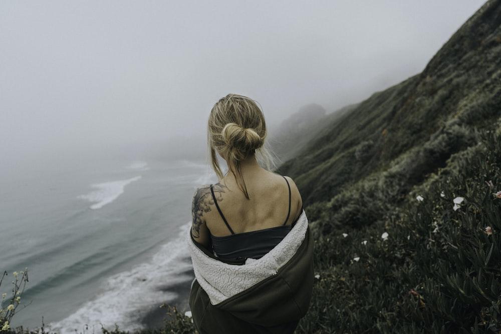 woman standing on cliff near beach