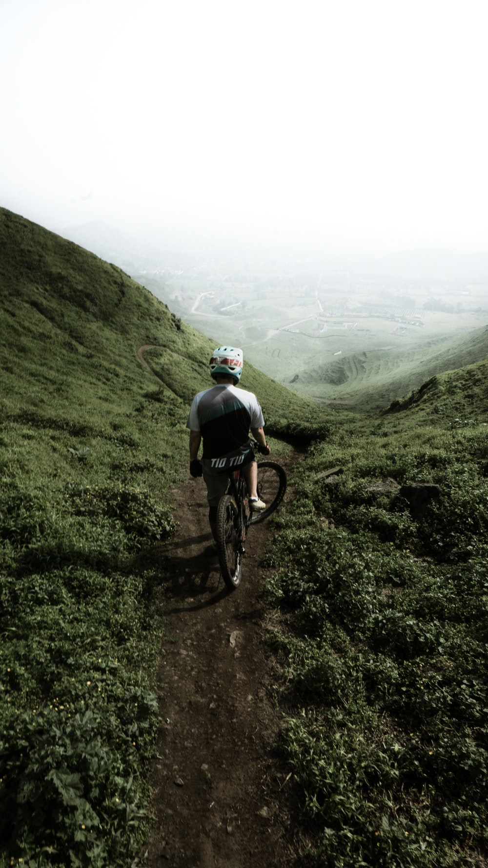 man riding bike on hill under white sky