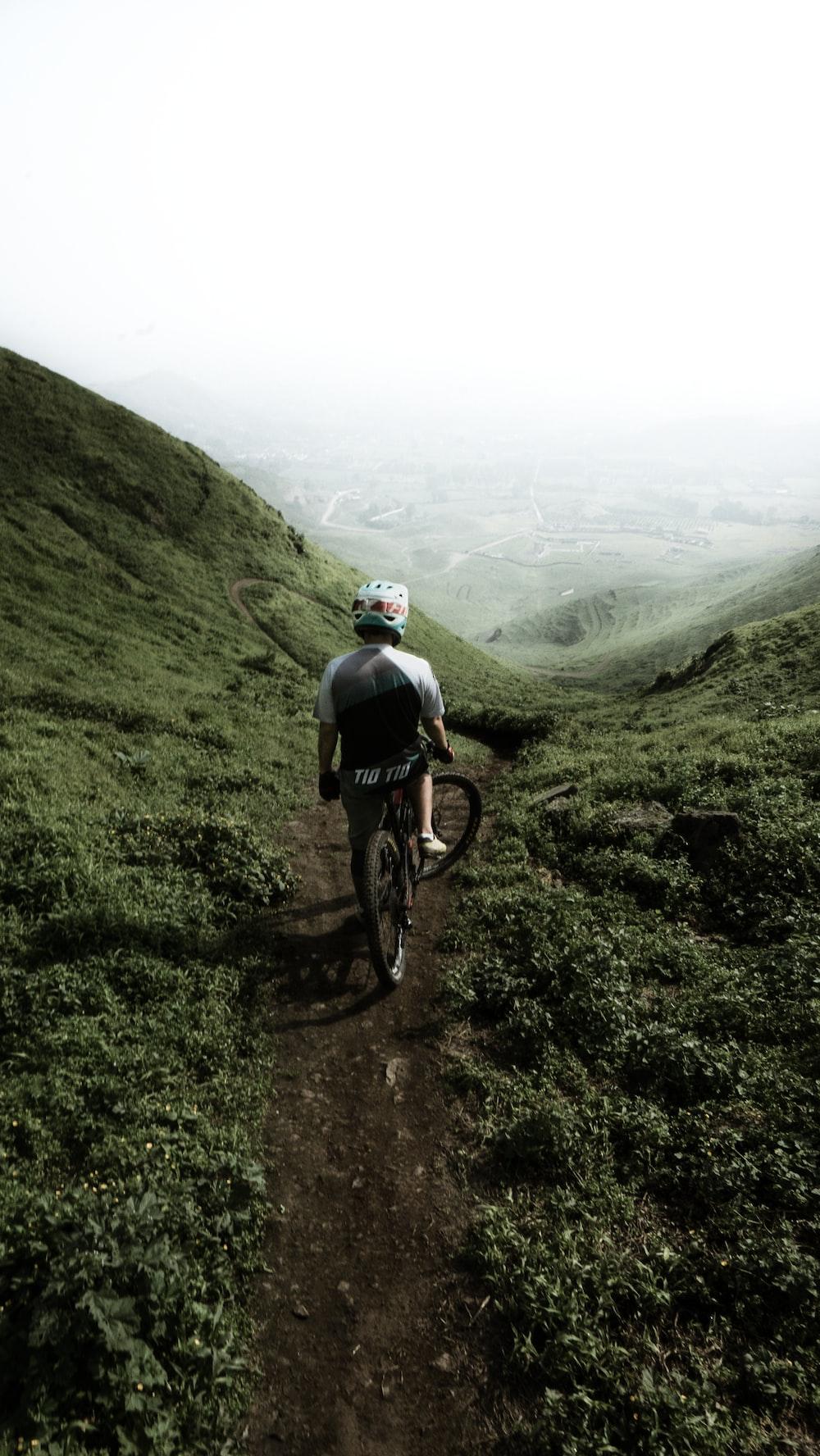 man riding bike on hill under white sky