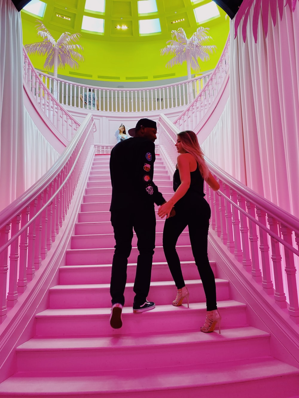 man and woman climbing stairs while holding hands