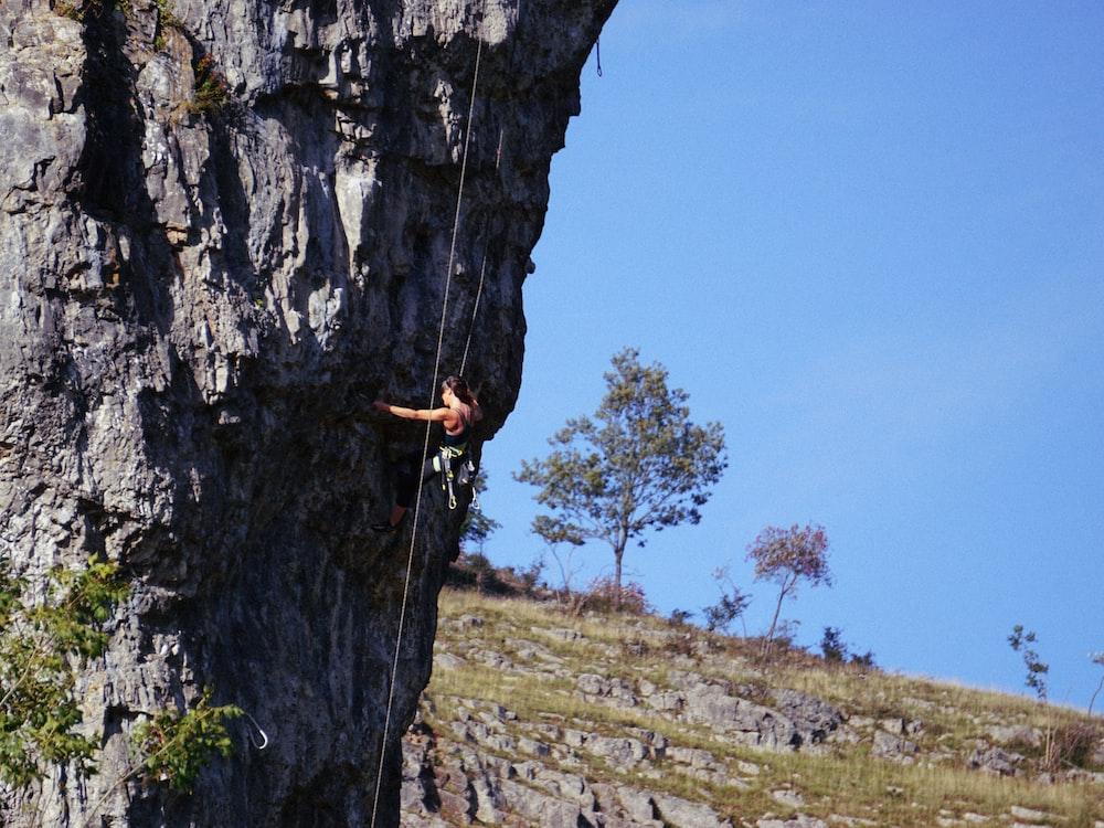 person rock climbing under blue sky