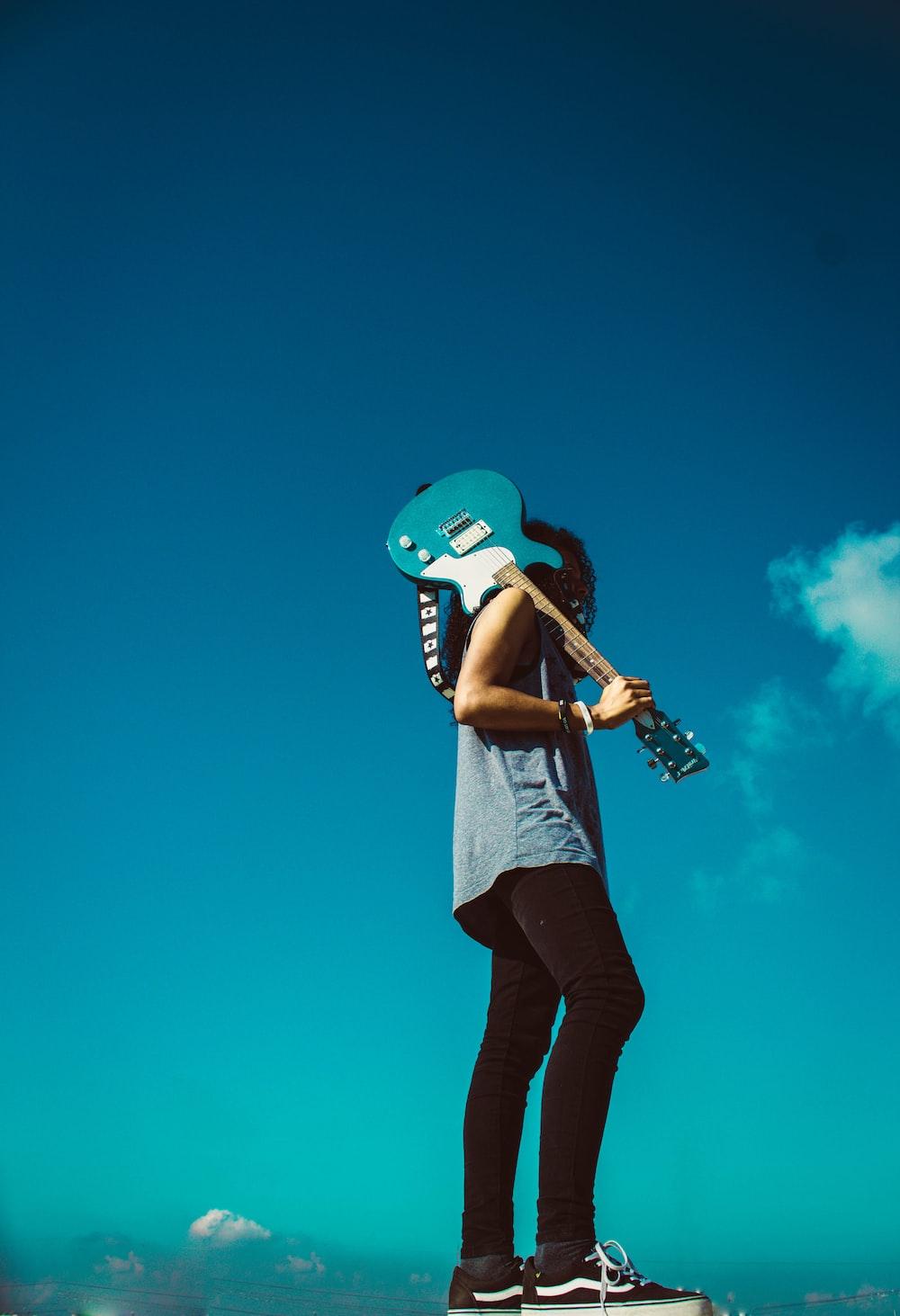 man holding blue guitar