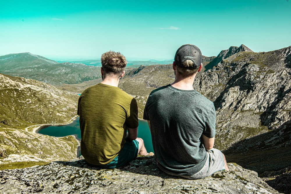 two men sitting on cliff during daytime
