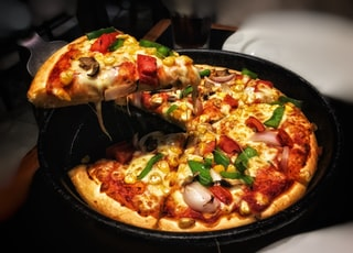 brown pizza on black plate