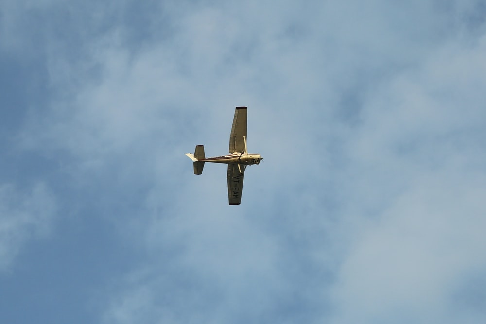 brown airplane flying under white clouds