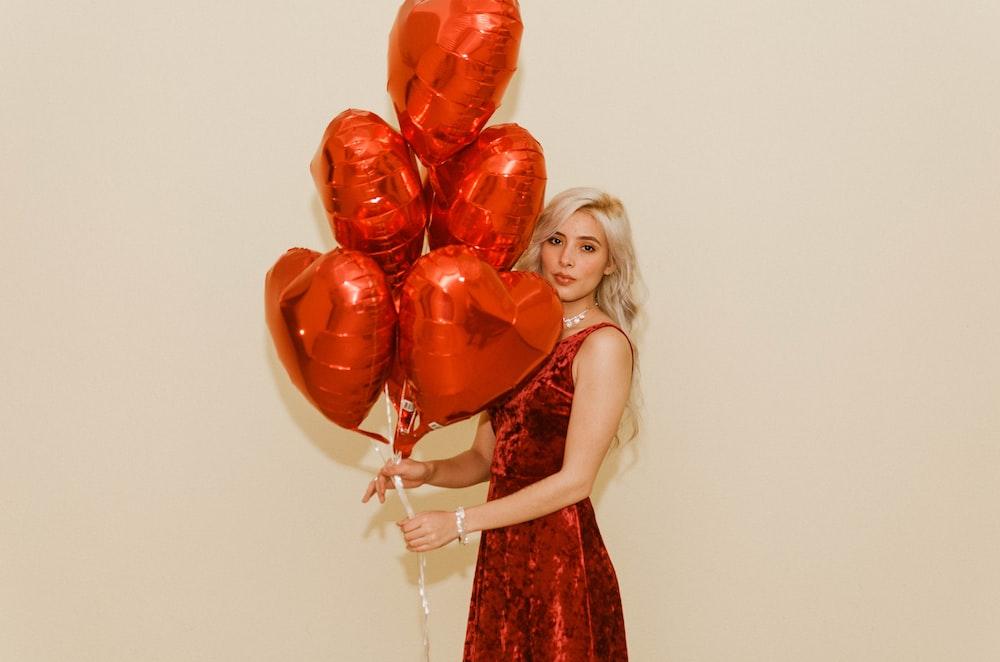 woman holding heart balloons