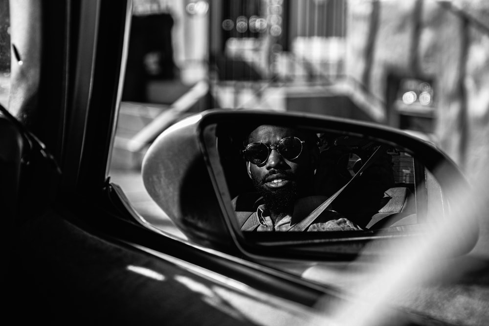 grayscale photography of man sitting on vehicle seat