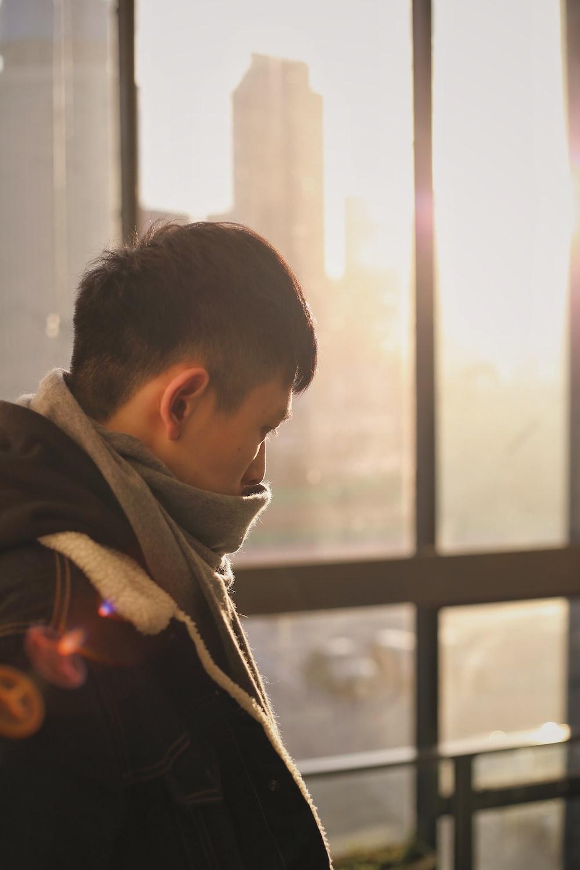 man wearing grey jacket standing near the glass window