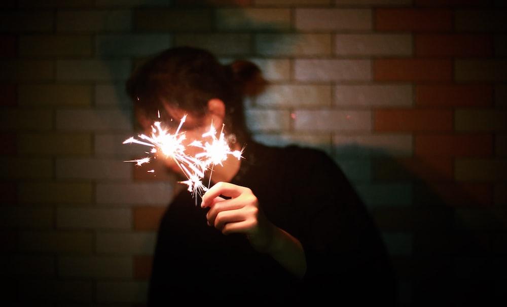 man holding lighted sparkle