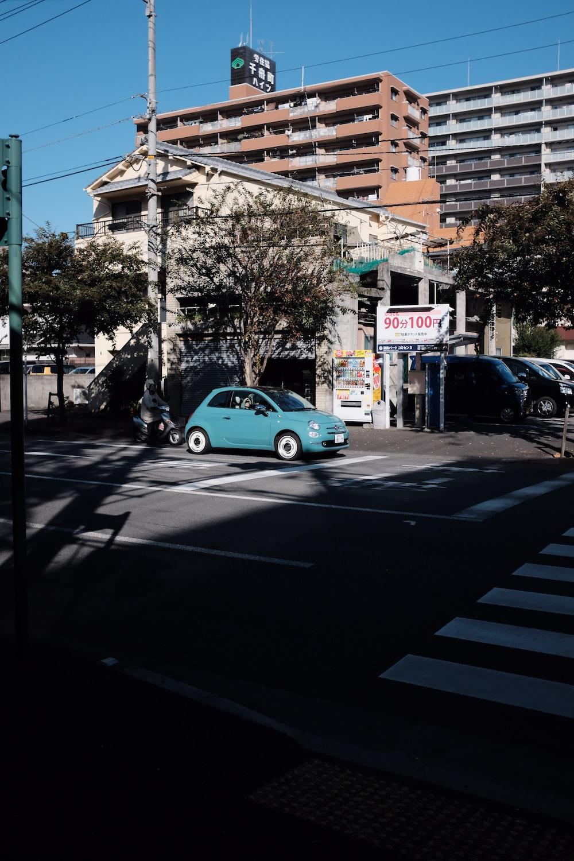 blue car parked beside building