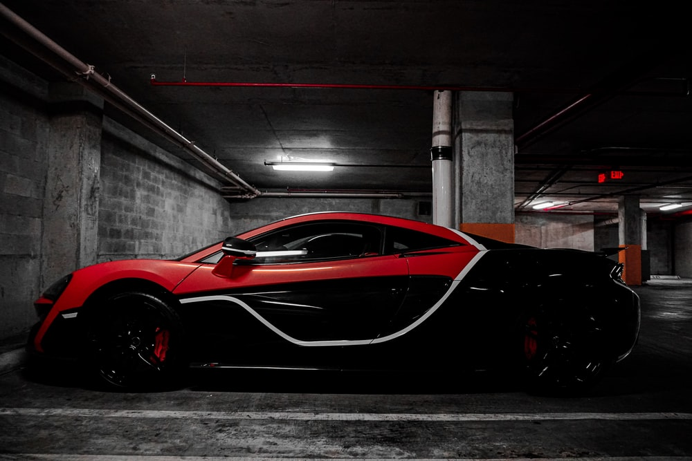 red and black sports coupe parked front of wall