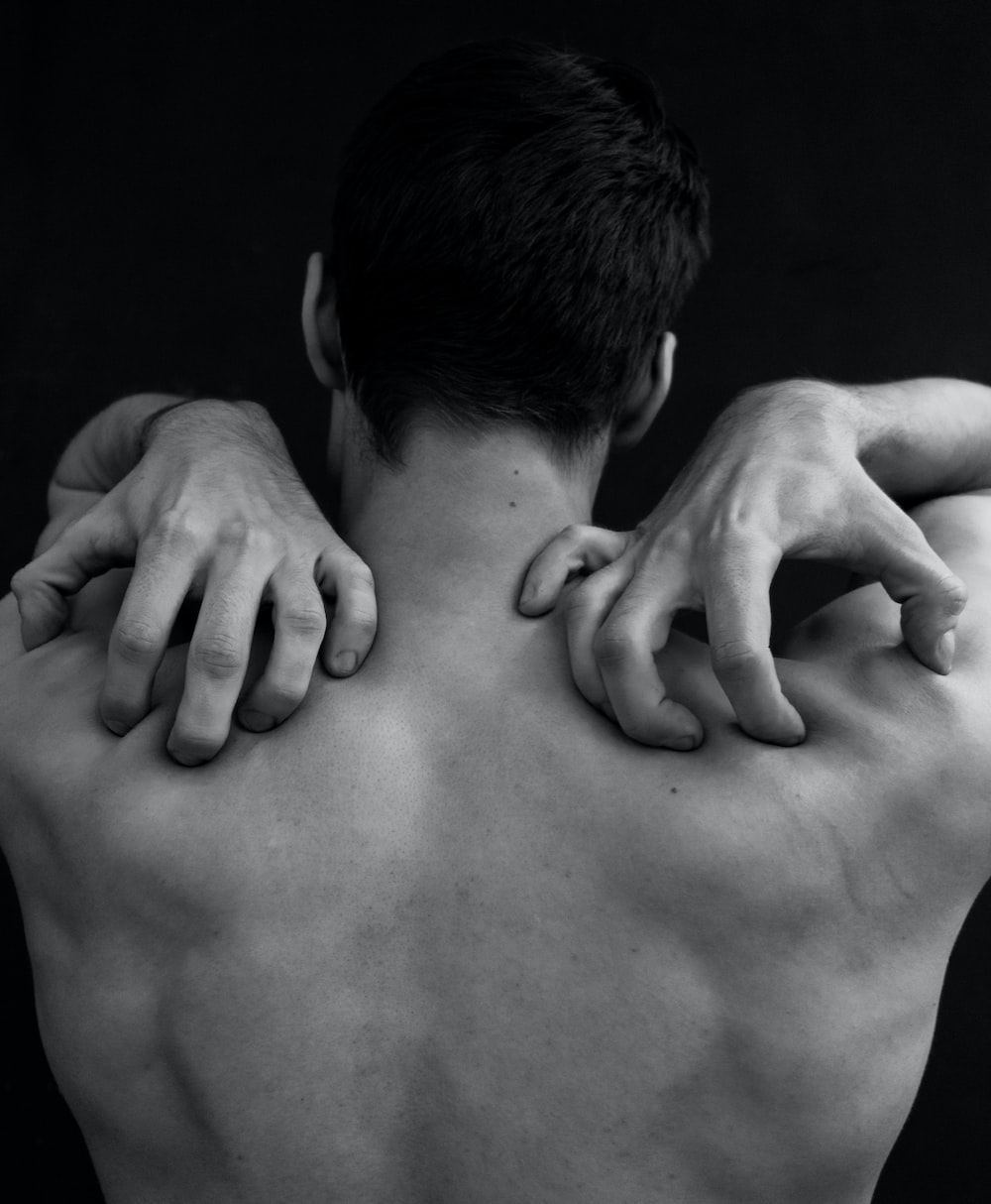 grayscale photography of man holding his shoulder