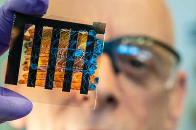 NREL researcher holds a perovskite ink painted cell.     NREL researchers have developed an interdigitated back contact solar cell design in which the metals and transport materials are solution processed by either ink jet or spray coating. Combined with a perovskite ink formulation with a low boiling point (<80 C) allows