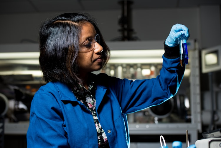 A woman who appears to be of Indian decent wearing a blue lab shirt and holding a test tube of liquid.