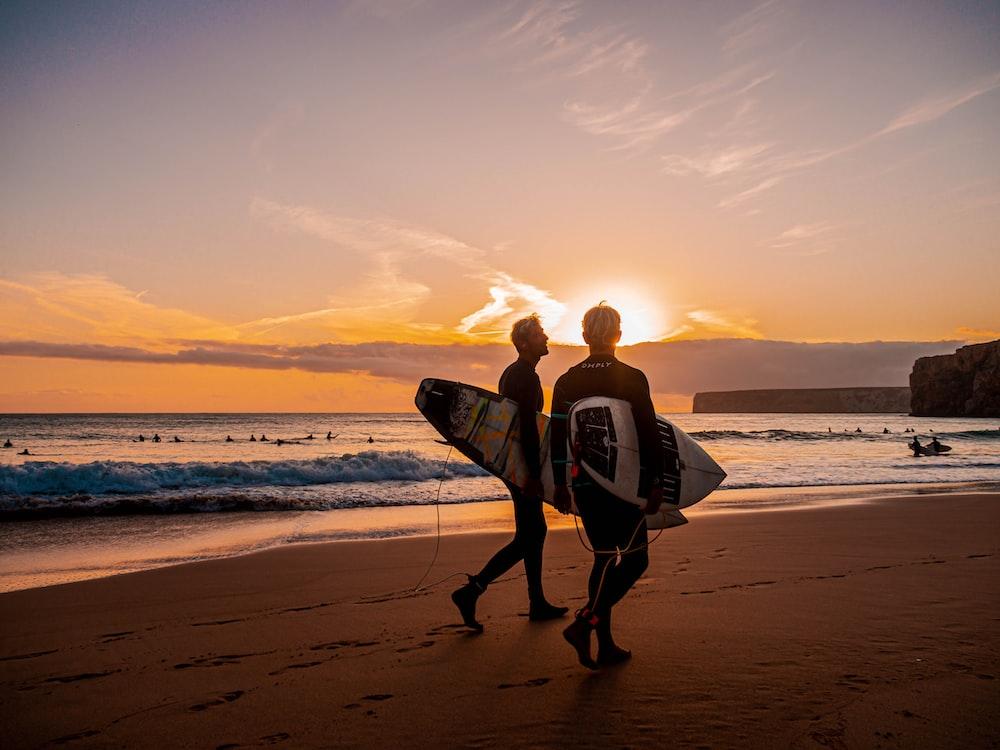 two person holding surfboard walking on seashore