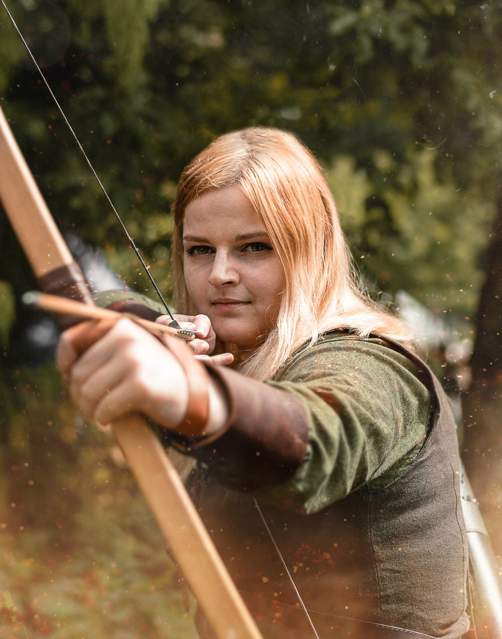 woman wearing gray vest and green shirt using brown wooden composite bow