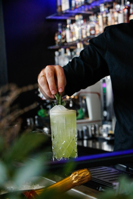 man making drink inside bar
