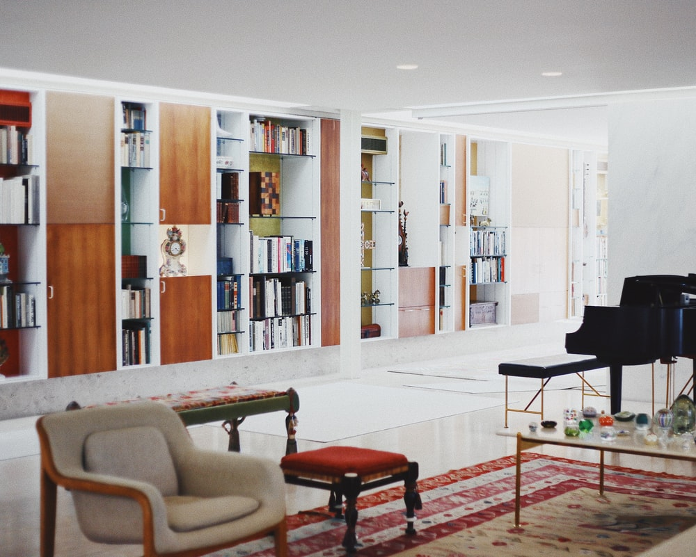 black upright piano in living room in front of bookshelf