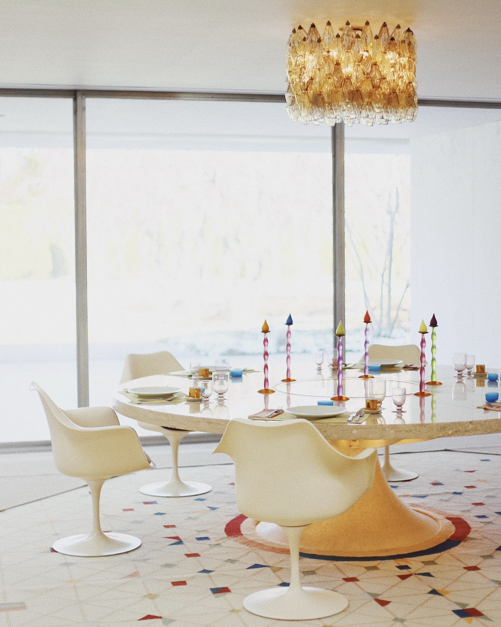round white and brown table with chairs under glass chandelier