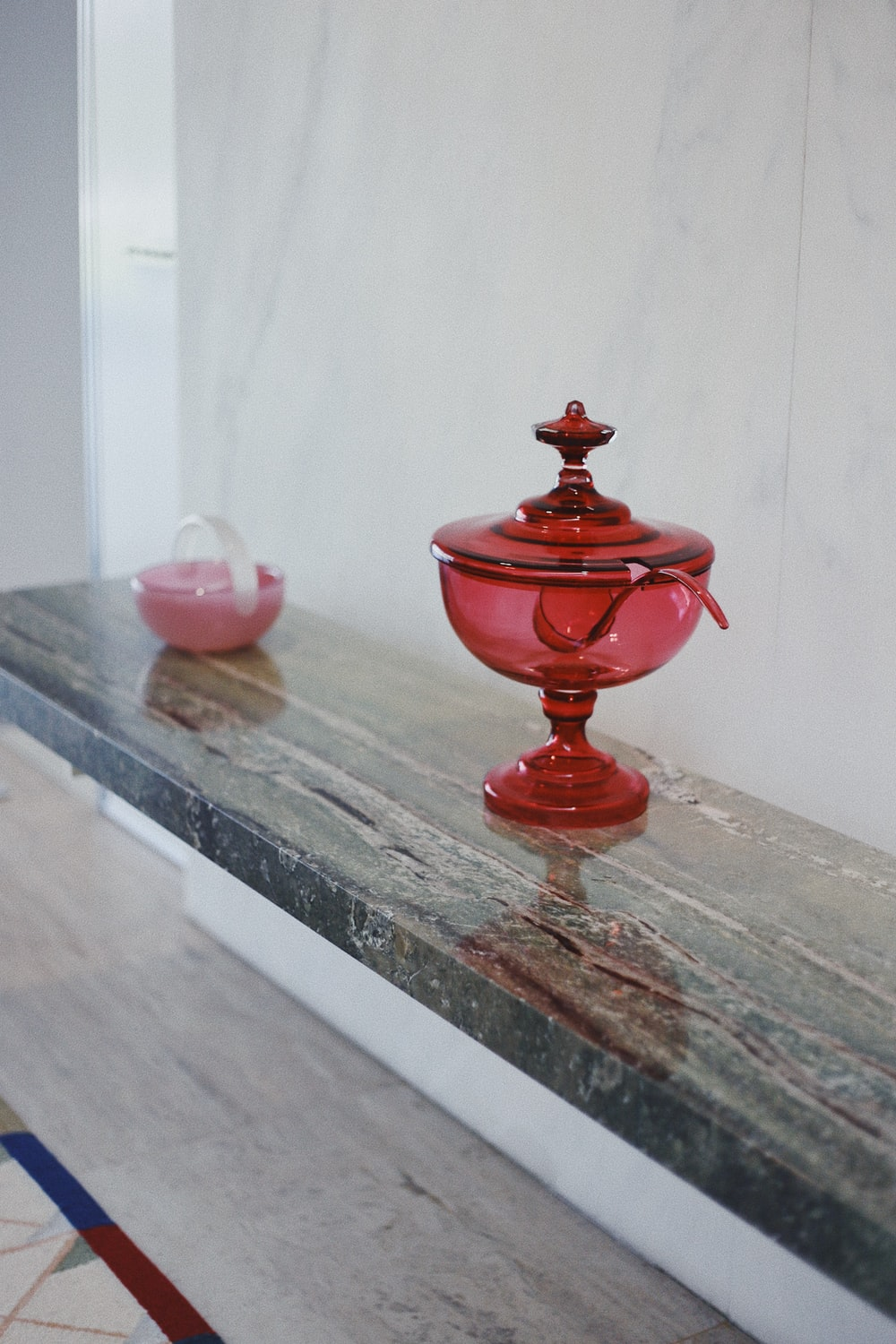 red footed glass jar with lid on rectangular gray wooden shelf