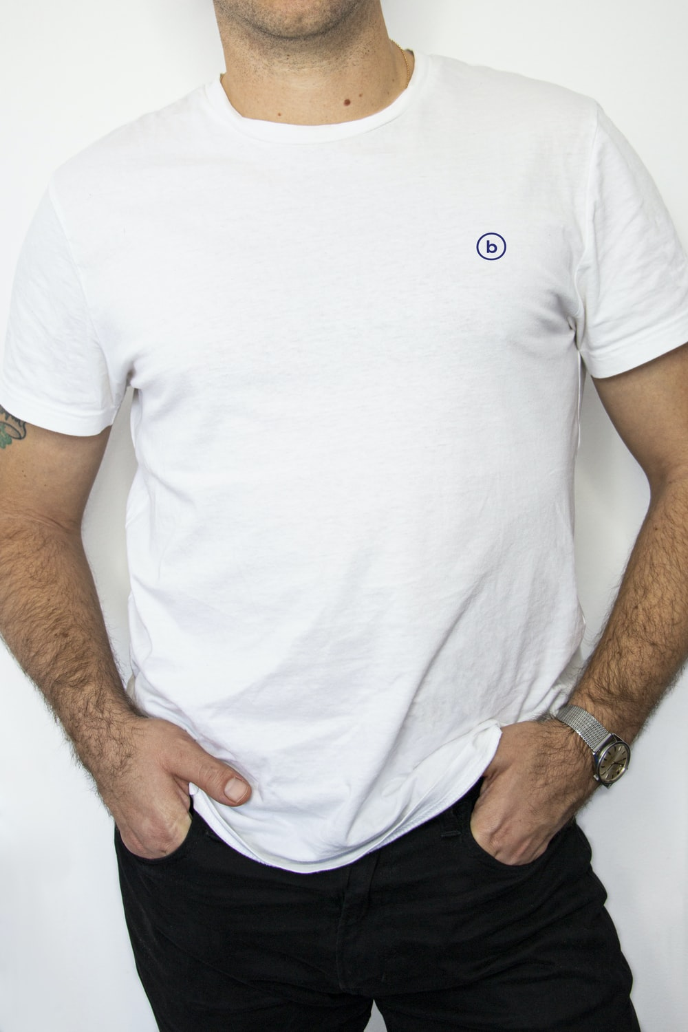 man wearing white crew-neck shirt and black denim jeans with hands in pocket