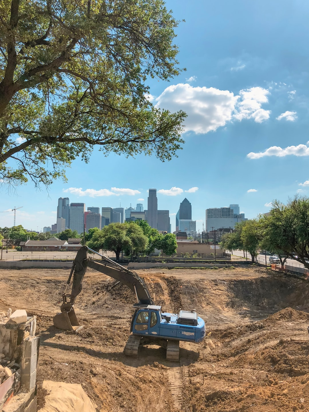 A construction zone near downtown Dallas with a blue excavator