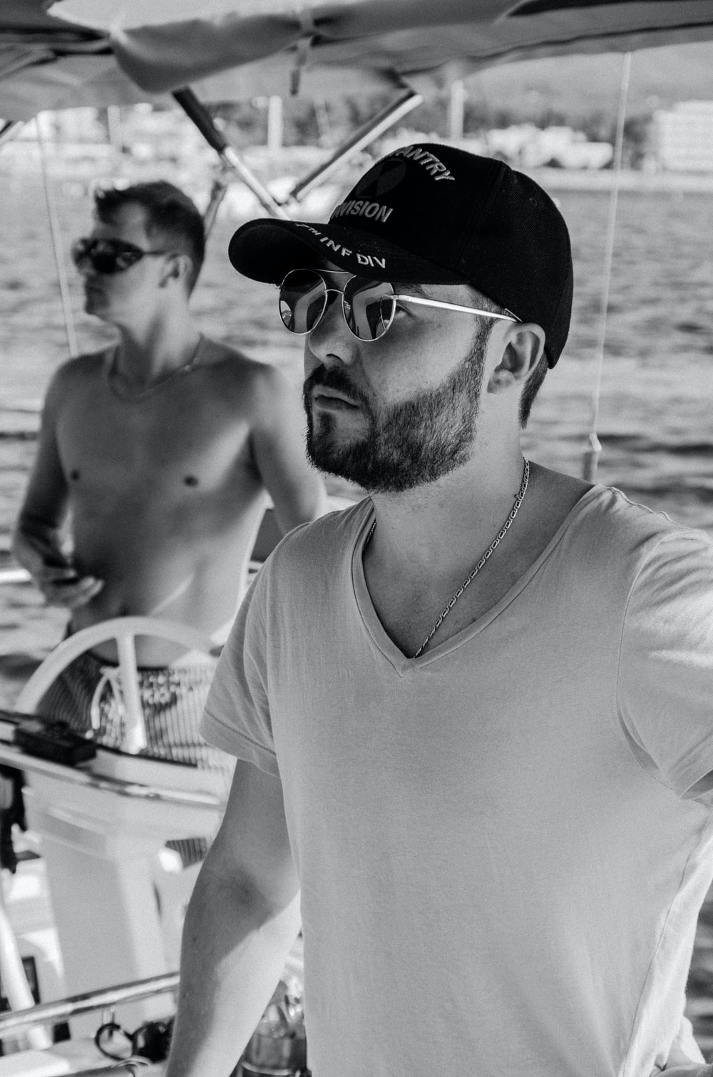 grayscale photo of man riding yacht