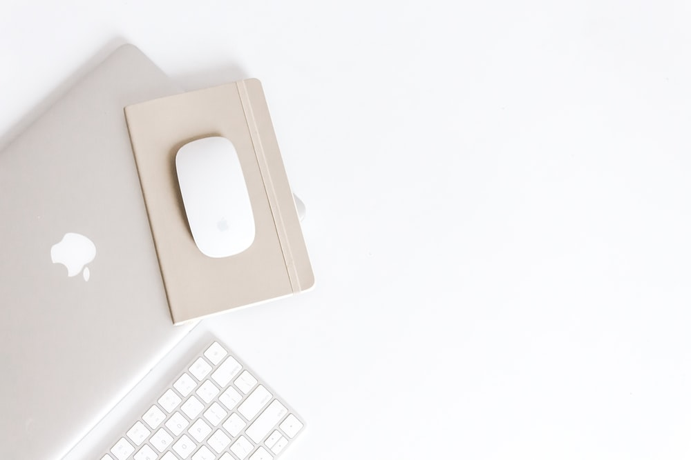 Apple Magic Mouse on beige notepad