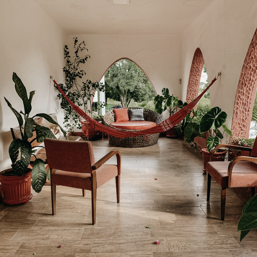 brown hammock near chairs and plant during daytime