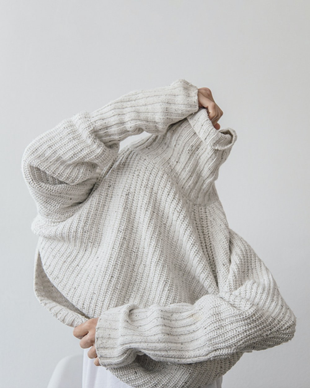 person wearing grey knit sweater
