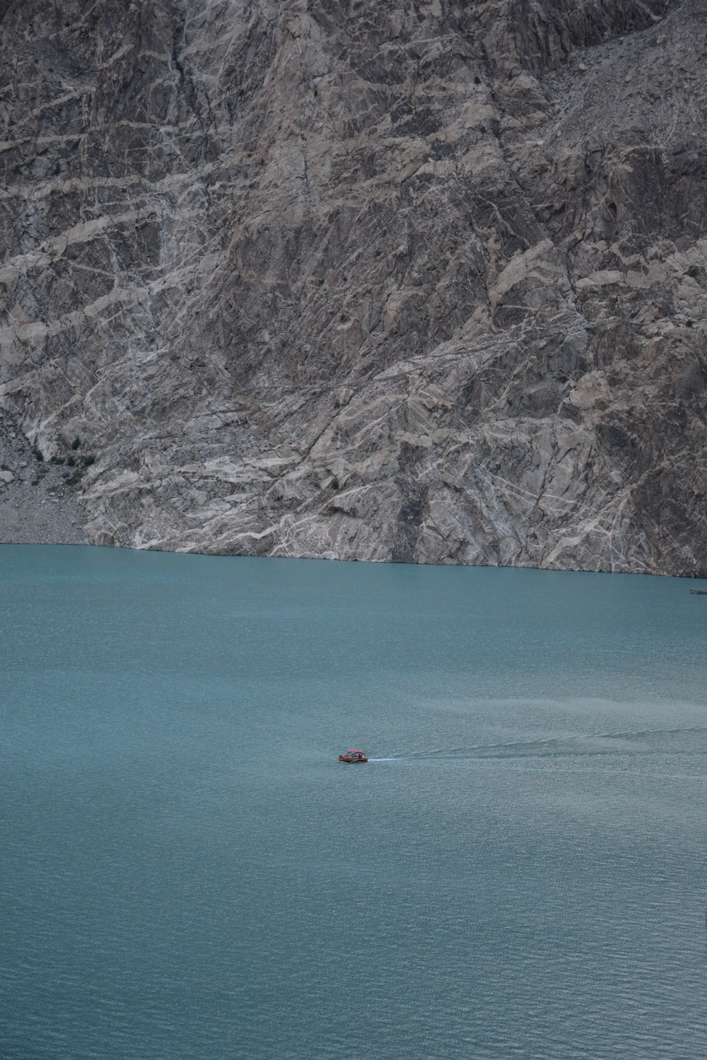 boat on lake near cliff