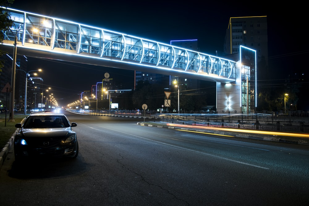 black vehicle parking near road during night time