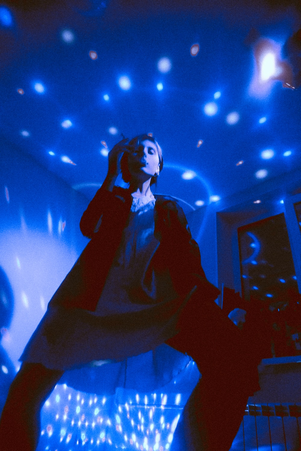 woman standing while dancing with blue LED lights background