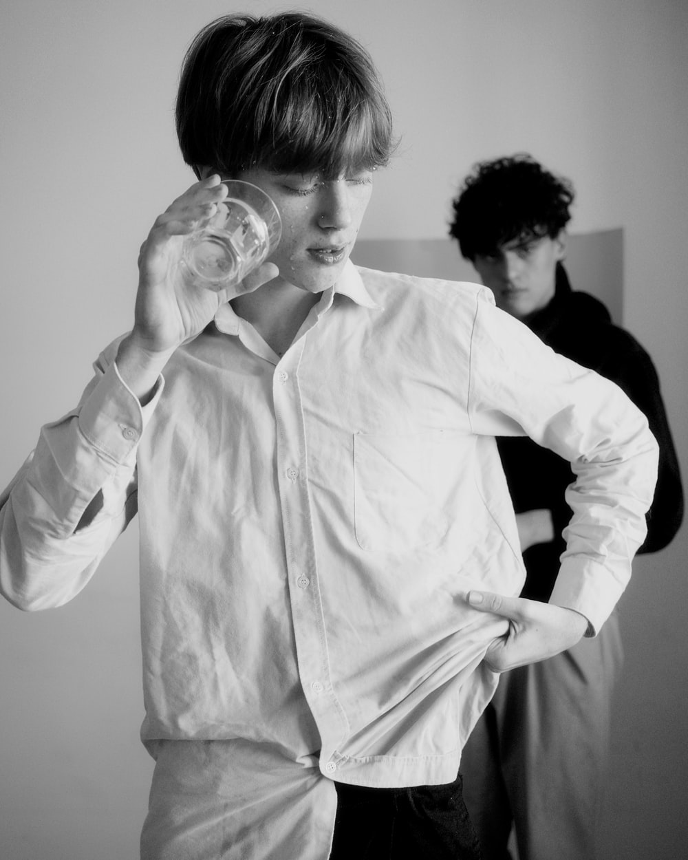 man holding clear drinking glass