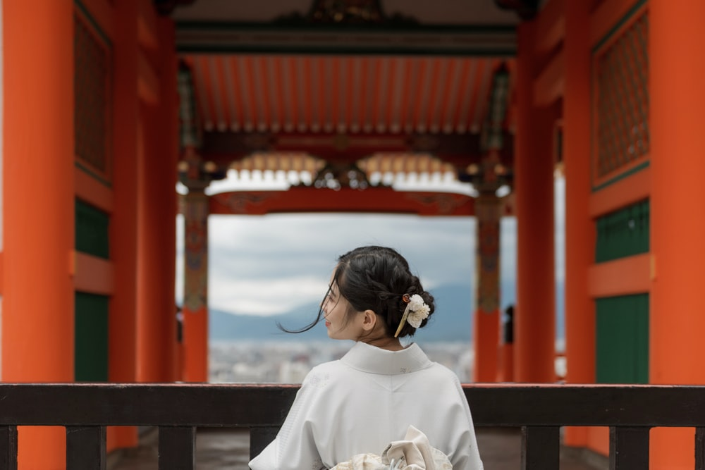 woman wearing white kimono standing while facing back near red building