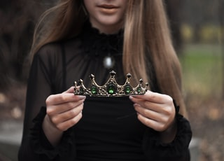 woman wearing black long-sleeved blouse standing while holding green and silver tiara