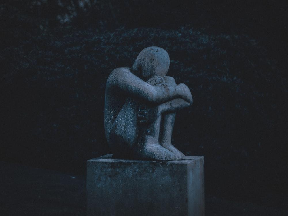man hugging his knee statue
