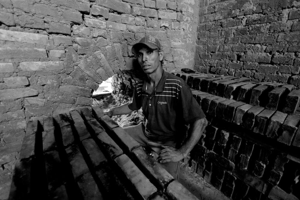 man sitting near bricked wall