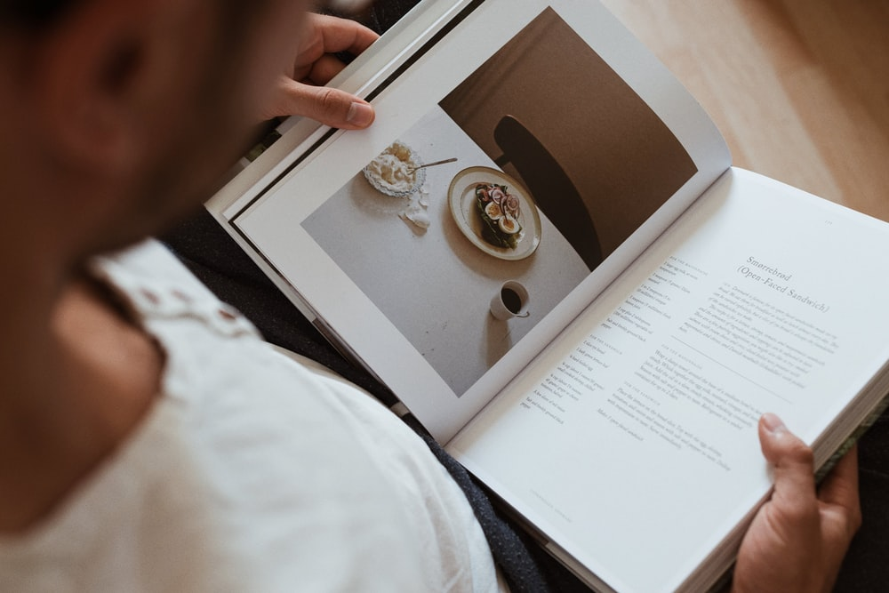 selective focus photography of man holding book