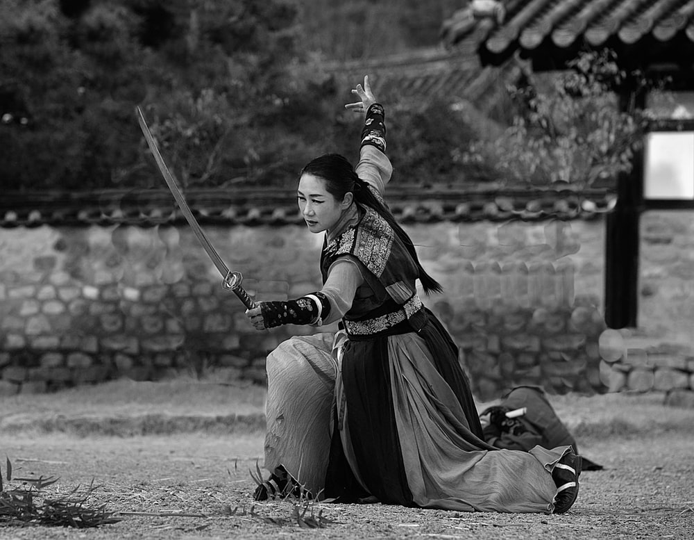 grayscale photo of woman holding sword