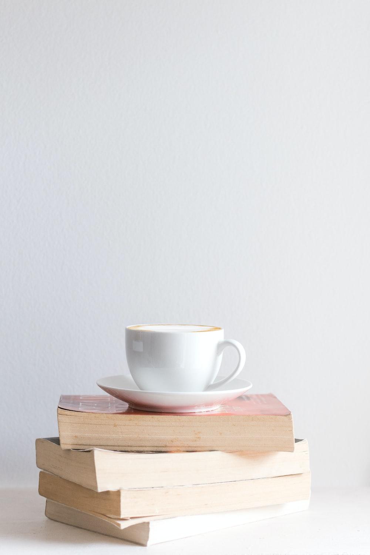 white mug with saucer on piled books