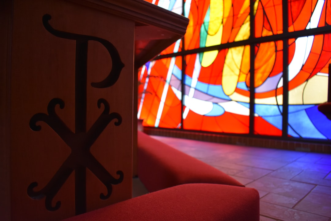 A close-up on a Chi-Rho in our communion railing, with one of our stained-glass windows behind.