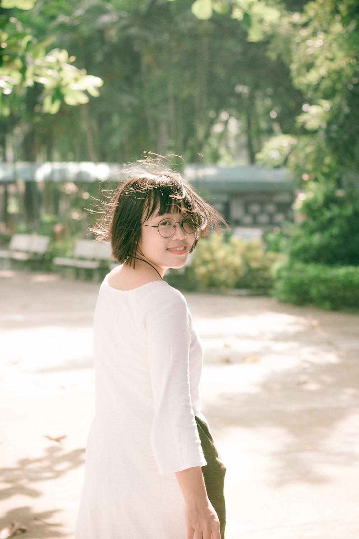 woman wearing white dress looking back while walking on street