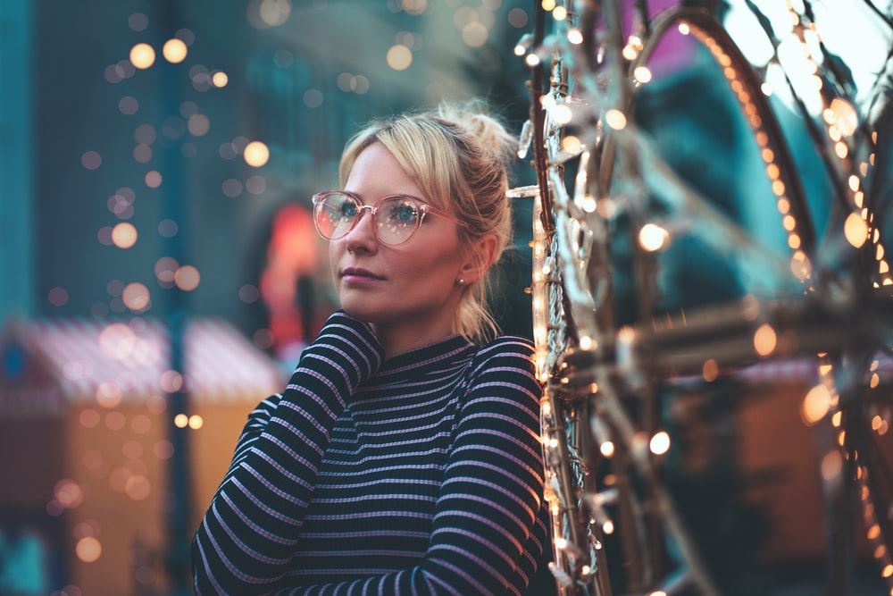 woman wearing black and white striped crew-neck long-sleeved shirt and eyeglasses standing near lighted string lights