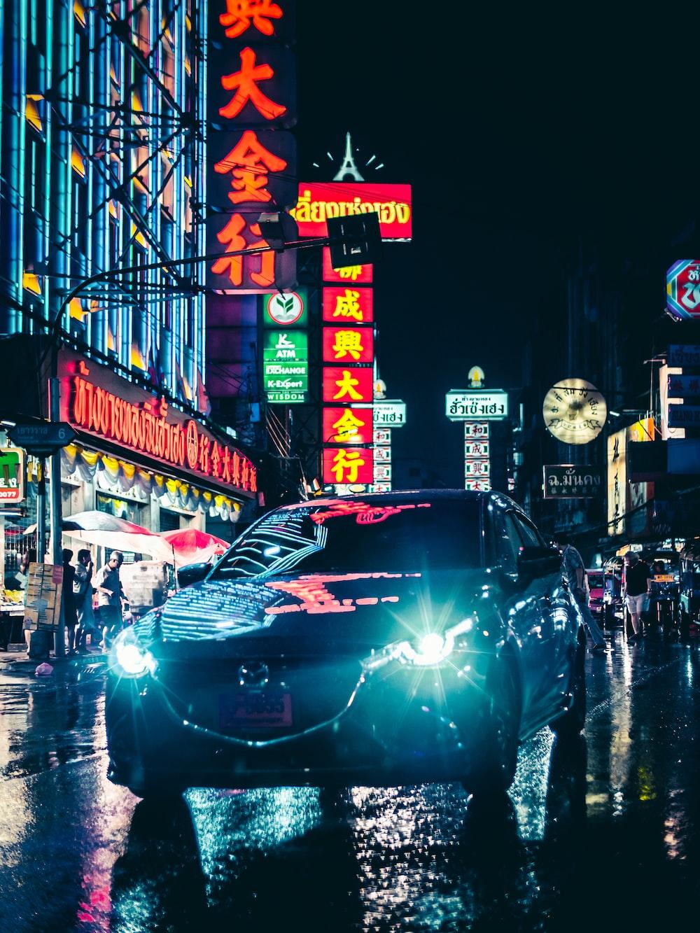 gray Mazda sedan on road viewing buildings during night time